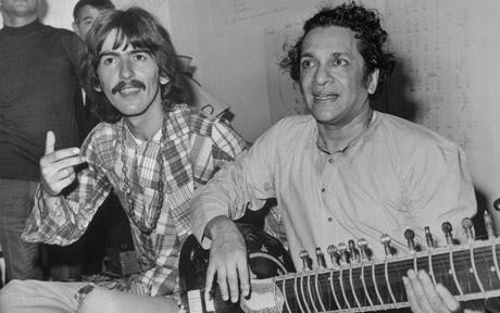 George Harrison and Ravi Shankar with a sitar in 19060s